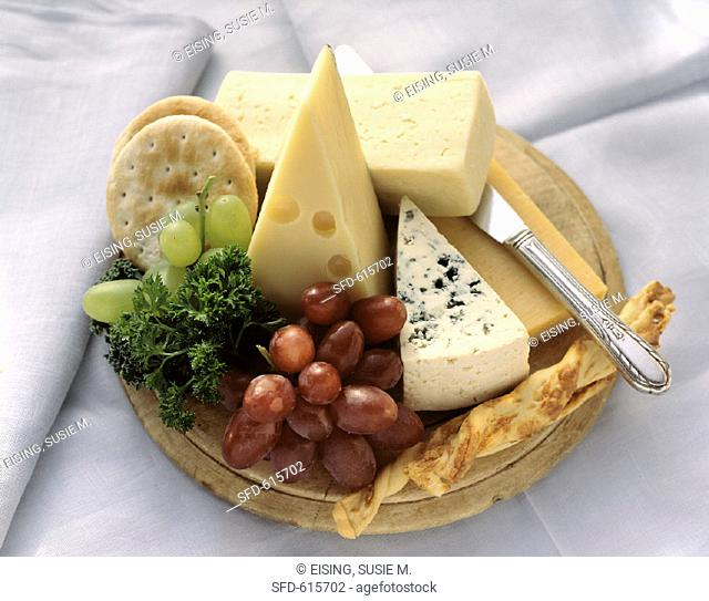 Assorted Cheese Crackers and Grapes on a Cutting Board