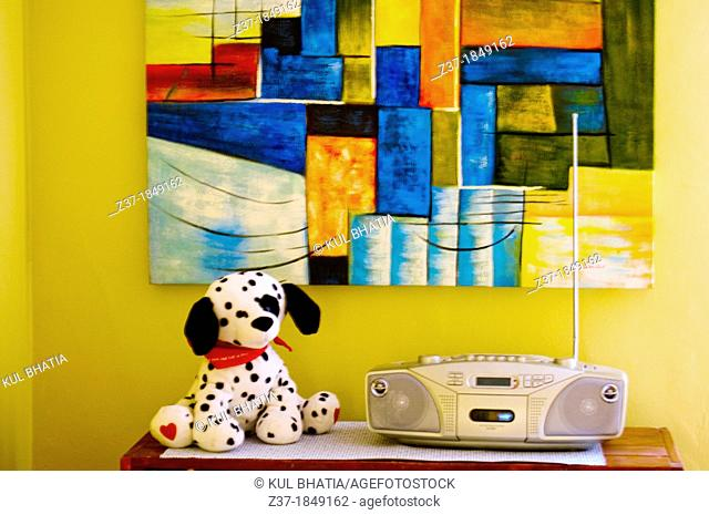 A stuffed Dalmatian dog sits next to a music box, a multi-colored painting on the wall, Canada