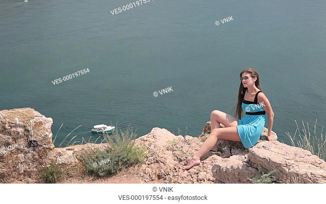 young woman Resting on the cliff near the Black Sea, Bay of Balaclava, Crimea In the background, a pleasure boat sails