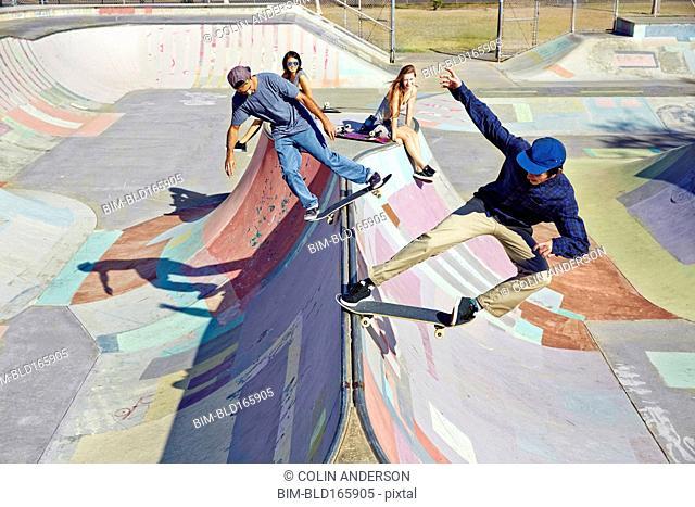 Women watching men on skateboards at skate park