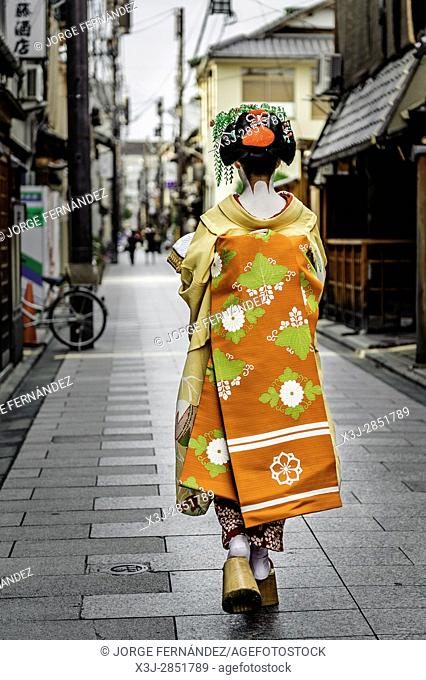 Maiko dressed with traditional attires posing to the camera in a small alley on her way to work