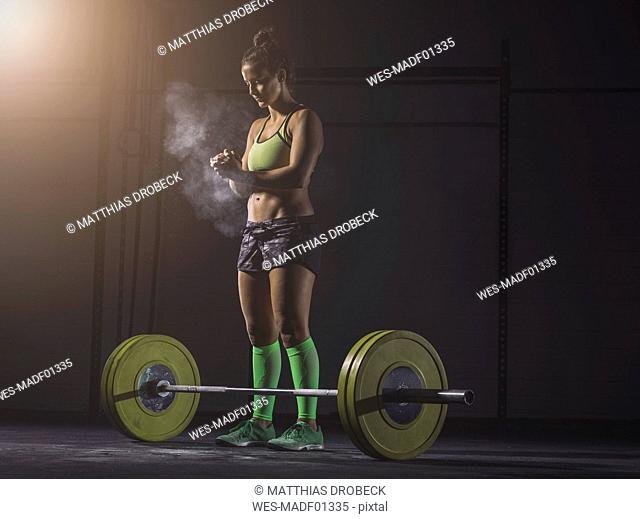 Young woman preparing to lift barbell