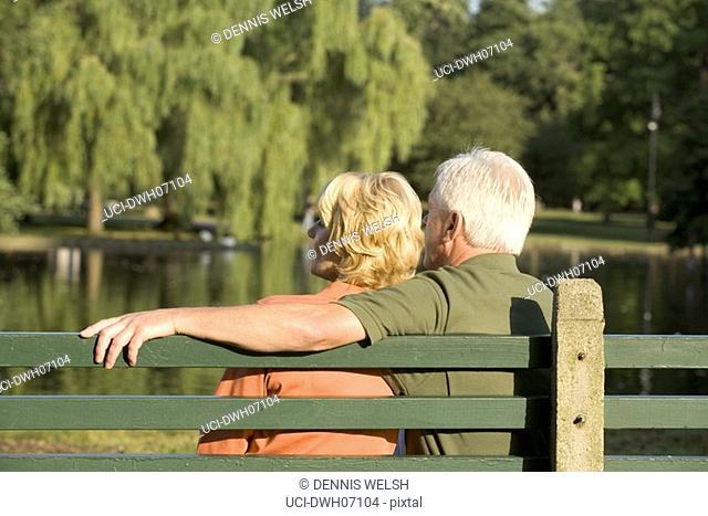 Senior couple cuddling on bench