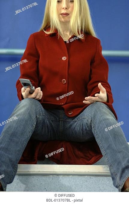 woman in jeans and red coat sitting on stairs with mobile in hand