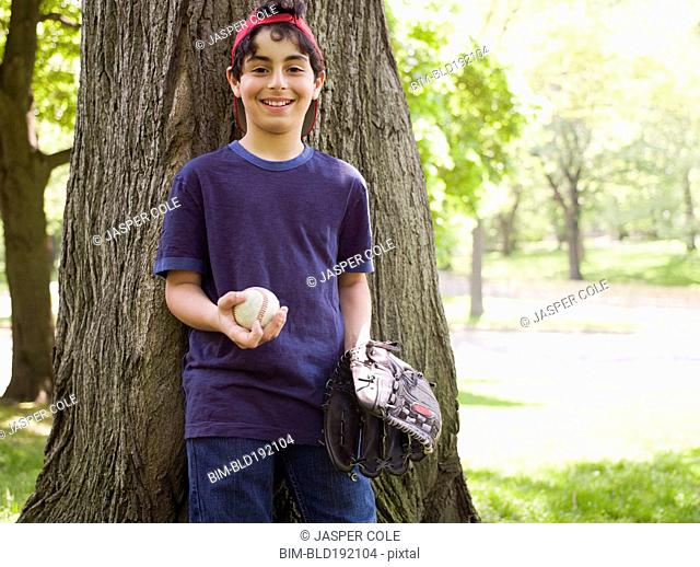 Smiling mixed race boy holding baseball and glove