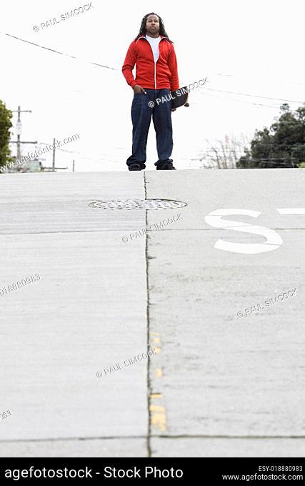 Teen Boy Holding Skateboard