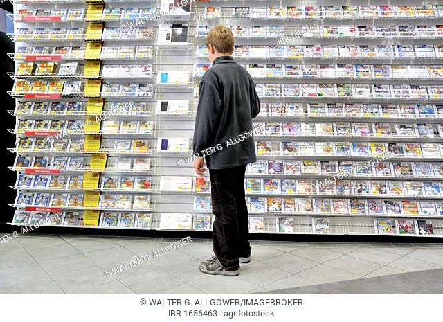 Ten-year-old boy boy in a store with a large selection of Nintendo DS games, Germany, Europe