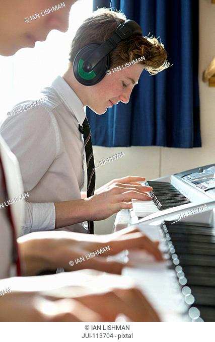 High school student with headphones playing piano in music class
