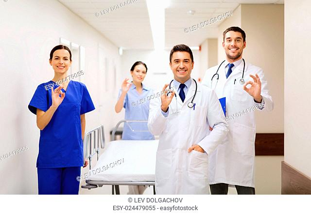 clinic, profession, people, health care and medicine concept - group of happy medics or doctors with gurney showing ok hand sign at hospital corridor