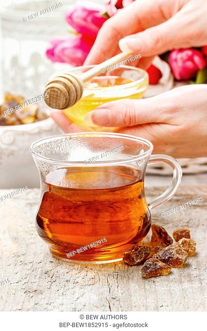 Pouring honey into glass of tea