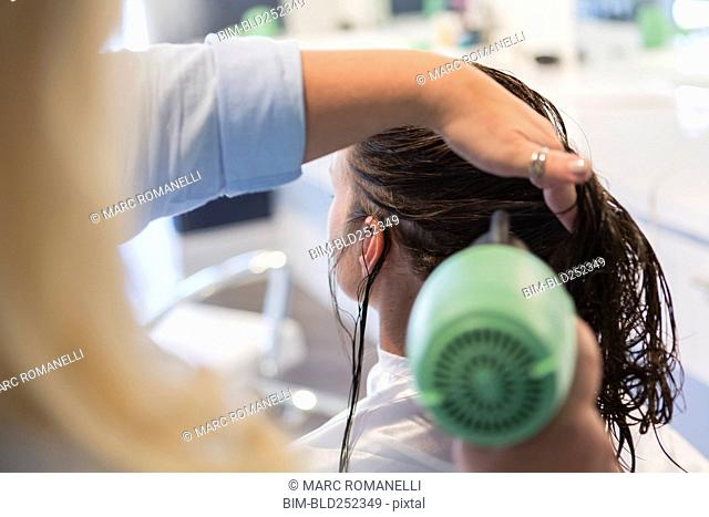 Stylist drying hair of woman