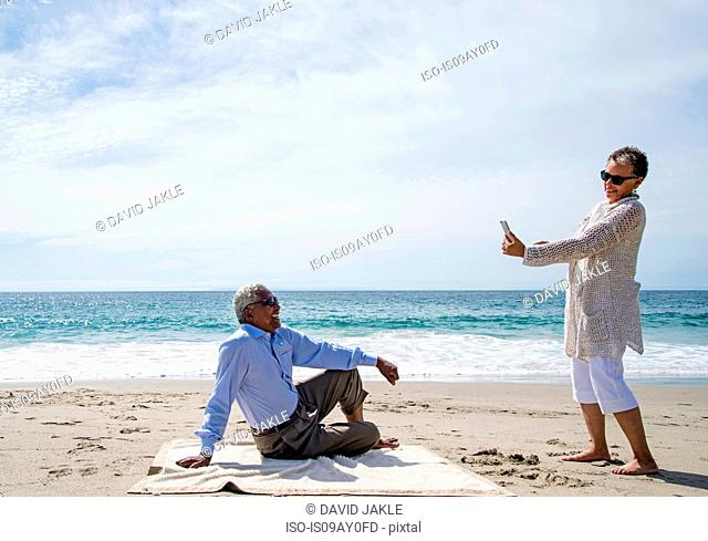 Senior couple on beach, woman taking photograph of man using smartphone