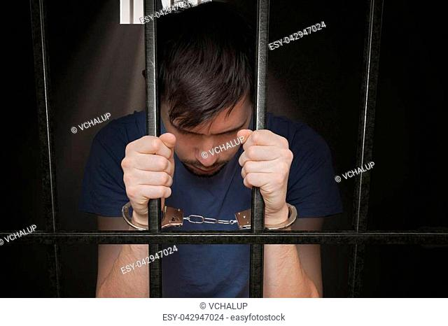Sad prisoner is holding bars in prison cell