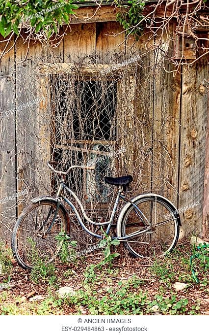 Antique one speed bicycle leans against abandoned building