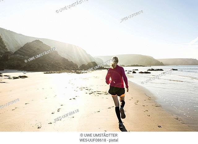 France, Crozon peninsula, teenage girl running on the beach