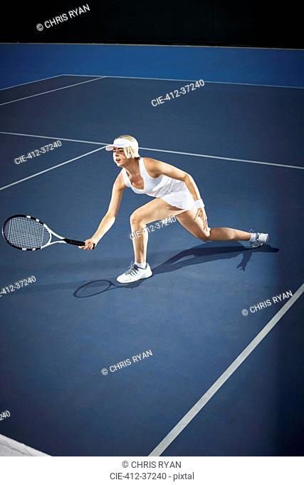 Young female tennis player playing tennis, reaching with tennis racket on blue tennis court