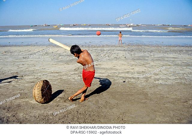 Children playing cricket on beach