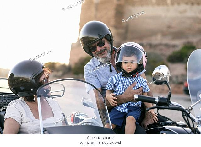 Spain, Jaen, grandfather, grandmother and grandson on motorcycle with a sidecar