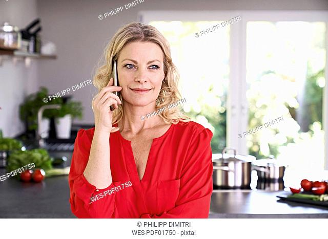 Portrait of smiling woman on the phone in kitchen