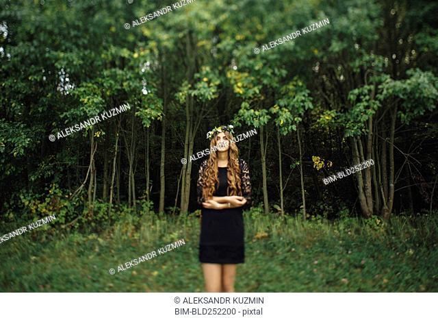 Middle Eastern woman wearing flower crown in woods