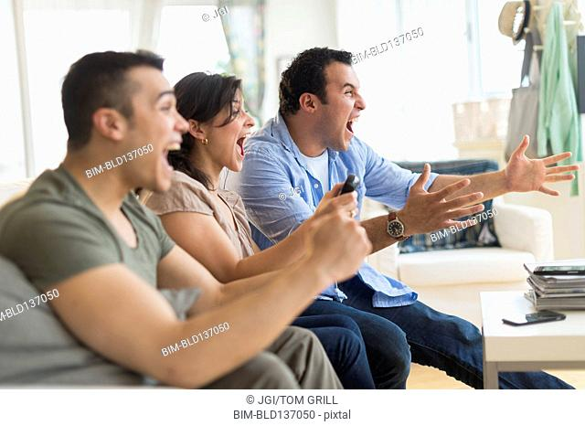 Hispanic friends cheering at television in living room