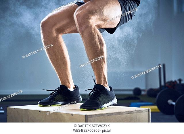Closeup of man doing box jump exercise at gym