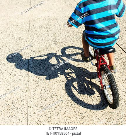 Low section of boy 6-7 riding bicycle