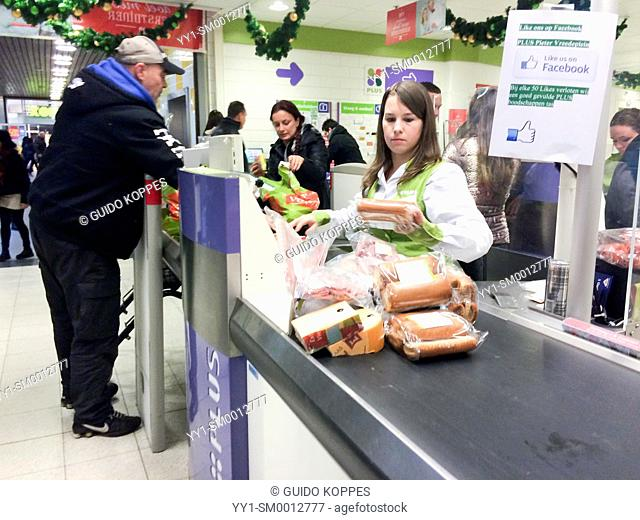 Tilburg, Netherlands. Cash register area of Supermarket 'Plus', quite buzzy, just before Christmas