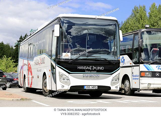 White Iveco Evadys tour bus parked on bus stop of a rest and service area on a day of summer in Salo, Finland - June 30, 2018.
