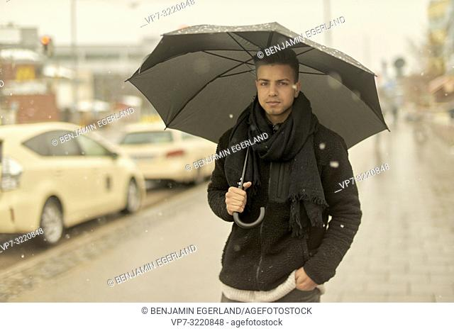 young man, Afghan ethnicity, with umbrella walking outdoors in city during winter, snowing, in Munich, Germany