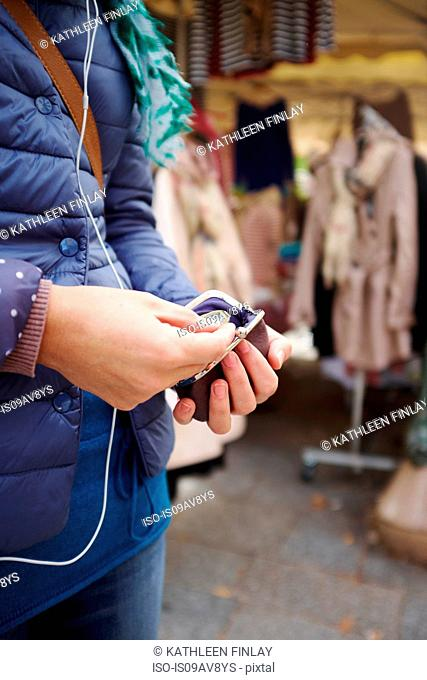 Young woman at market, taking money from purse, mid section