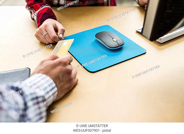 Close-up of two hands with credit card on desk