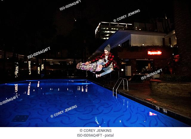 Male hipster skateboarder jumping above outdoor swimming pool at night