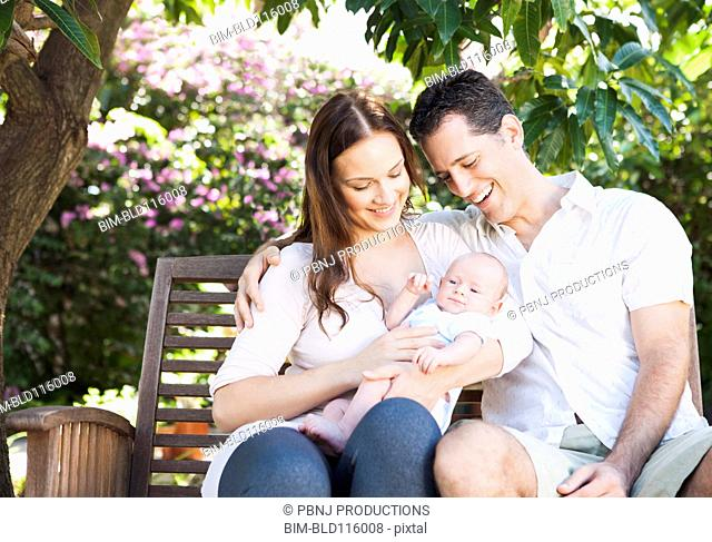Caucasian couple holding baby outdoors