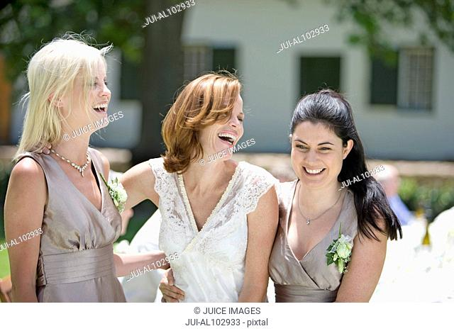 Bride with her bridesmaids laughing at wedding
