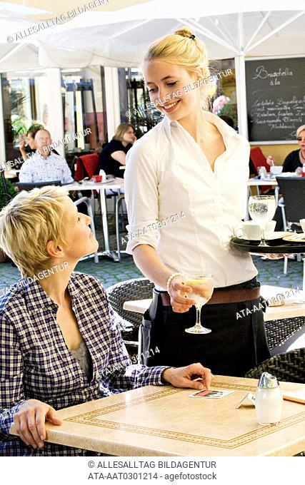 Young waitress serving a customer