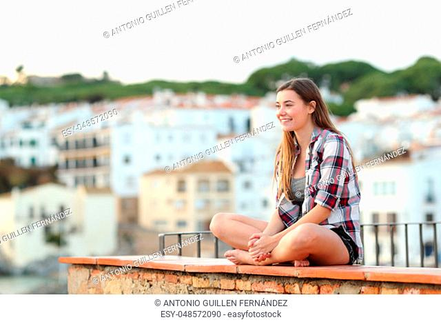 Happy teen contemplating views sitting on a ledge in a coast town on vacation