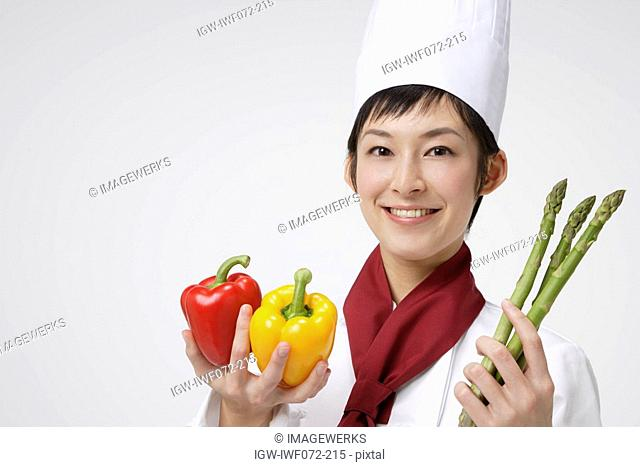 Female chef holding bell peppers and asparagus, smiling, portrait