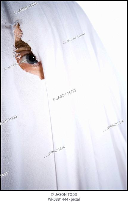 Portrait of a person looking through a hole in a sheet