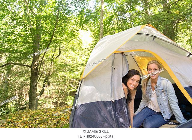 Two women sitting in tent in forest