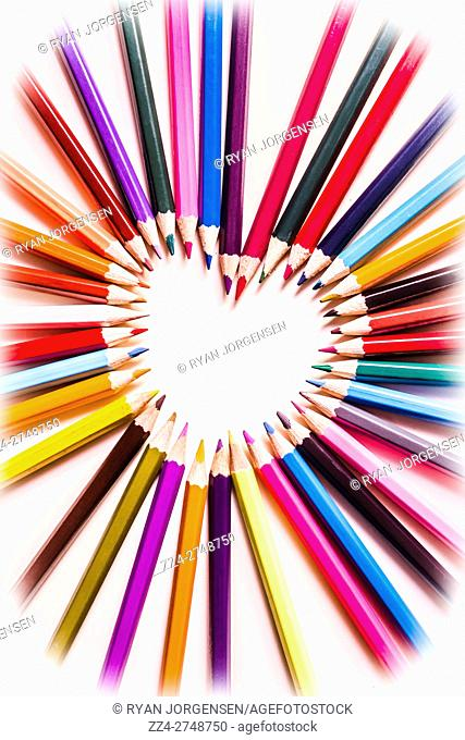 Arrangement of colored pencil crayons converging in a heart shaped center with blank copy space in a romance or love theme, overhead view on white with vignette