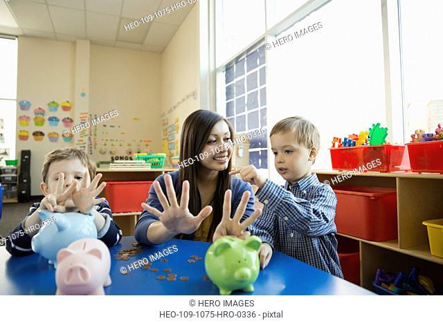 Boy counting on teachers fingers in school