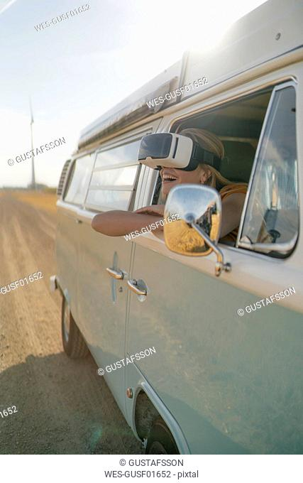 Happy woman wearing VR glasses leaning out of window of a camper van