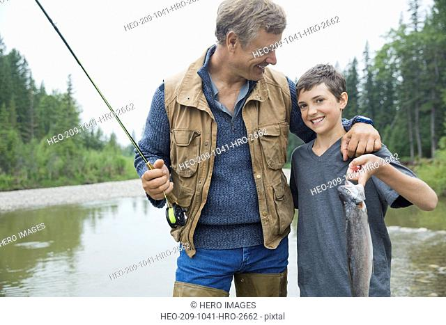 Father looking at son holding up fish