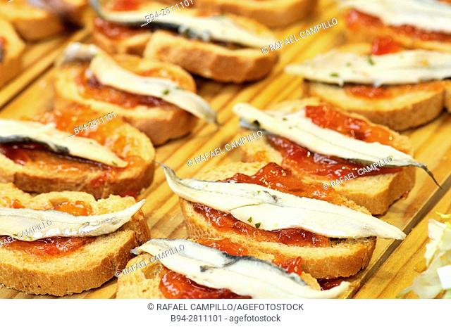 Montaditos, Pintxos or Tapas, bread with tomato and anchovies. Sant Josep market, aka La Boqueria. Barcelona, Catalonia, Spain