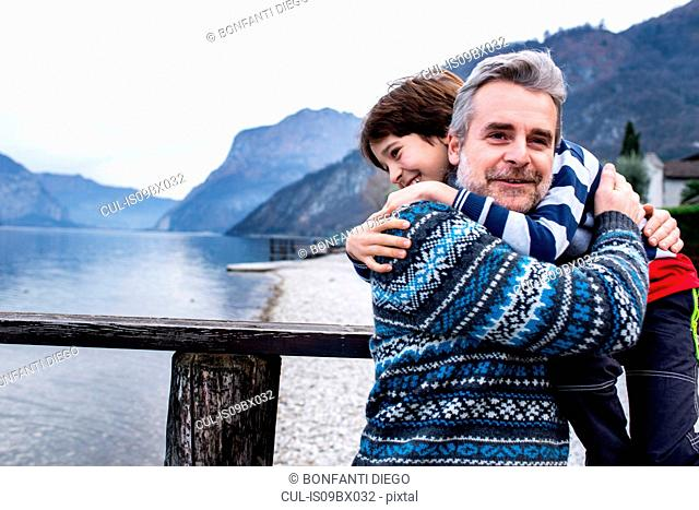 Boy and father hugging each other on lakeside pier, Lake Como, Onno, Lombardy, Italy