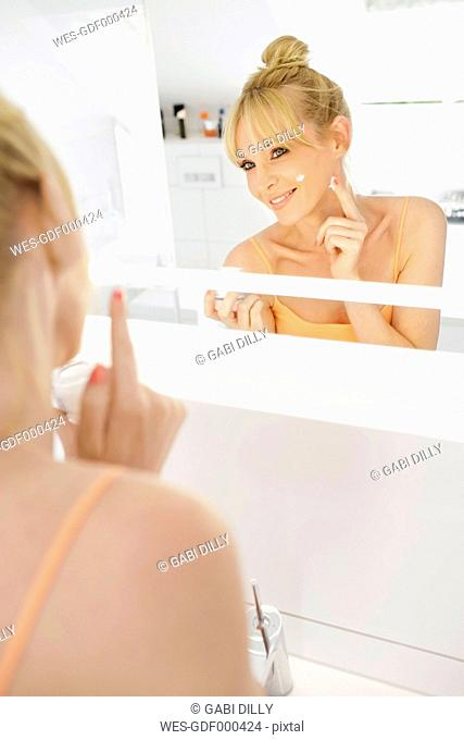 Smiling woman looking at her mirror image while applying face cream