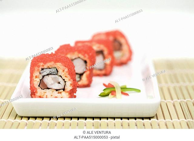 Maki sushi rolled in red flying fish roe, cross section view