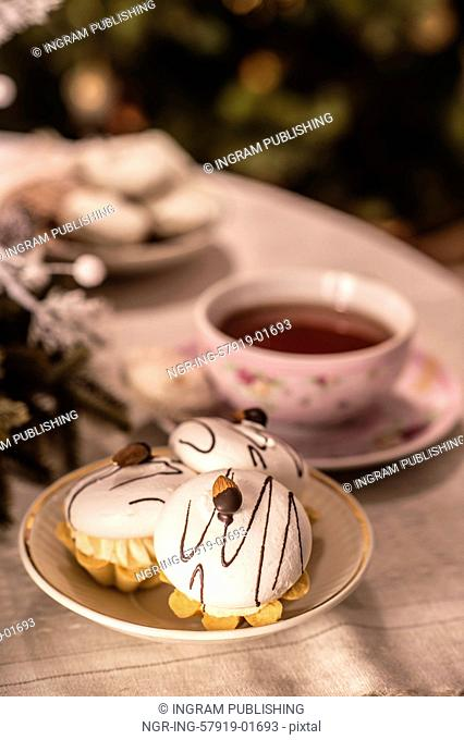 Tea cup and cakes on table in front of Christmas Tree
