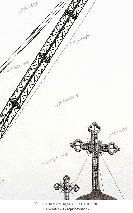Crane above the roof of an orthodox church having two metal crosses on its top - Buzau, Romania